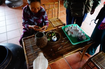 Hue rice museum - here this woman is showing us how a special herb is eaten during a traditional ceremony during which the parents of betrothed partners ate the herb, got buzzed, and discussed the arrangement and dowry before the marriage.